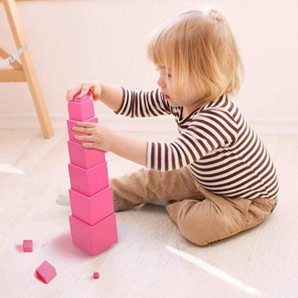 enfant jouant à la tour rose